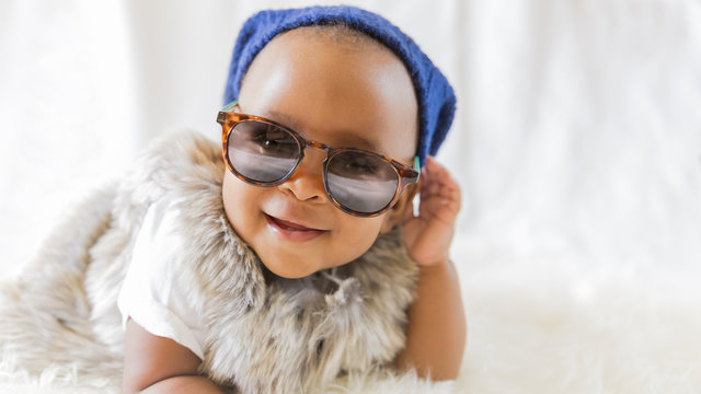 Super cute cool baby. Hipster baby in fur vest and sunglasses lies on a white bed in a room with curtains. Baby smiles while putting on sunglasses.