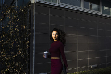 Cool young woman walking outside office building holding coffee mug