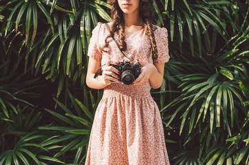 Beautiful girl with curly hair holds an analog camera