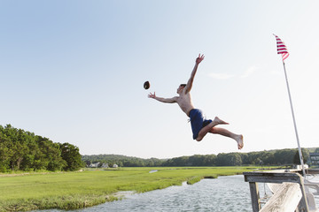 Teen Jumping off Dock to Catch a Football