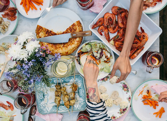 Overhead view of a table full of food with hands