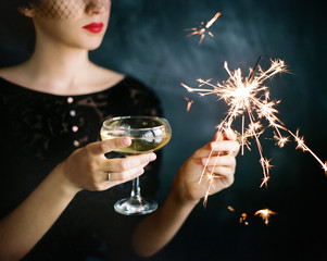 Crop female with champagne and sparkler