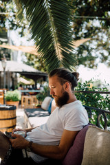 Young bearded man sitting in outdoor cafe