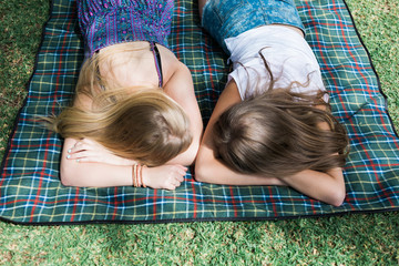 Looking down on two teenage girls lying face down on a picnic rug