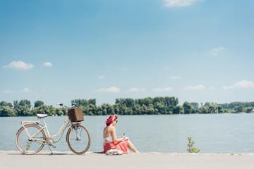 Young woman enjoying a sunny day at river bank and drawing