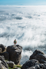 Male hiker with backpack on a mountain summit overlooking clouds