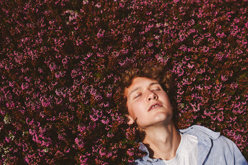 High angle view of young man relaxing on flower bed