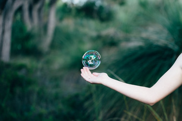 Girls hand reaching out catch a bubble in the bush