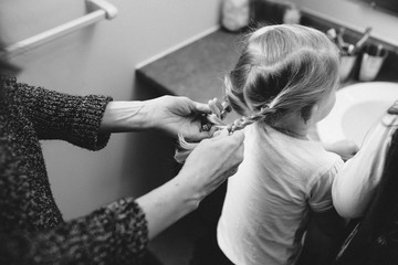 Young mother brushing duaghter's hair in the bathroom
