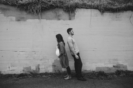 Pregnant couple leaning awkwardly by cement wall