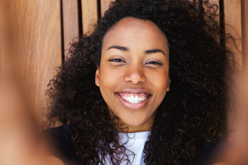 Closeup of a young african american woman taking a selfie on a wooden floor