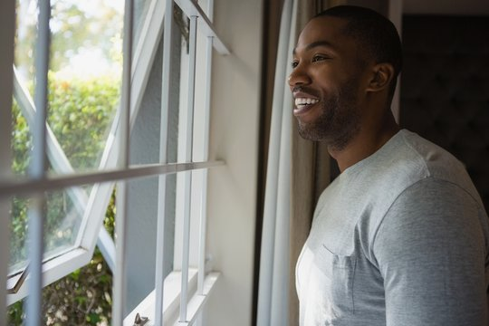 Thoughtful smiling man looking out through window at home