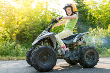 Fearless Girl Having Fun Riding Fast Gas Powered Kids ATV Quad On Trail With Sunflare on Cottage Road