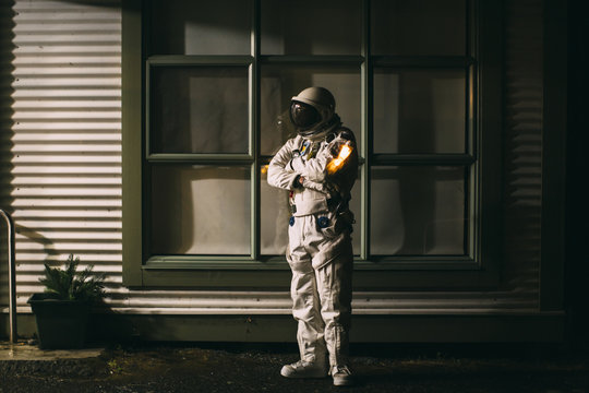 A spaceman stands tall and proud outside a house at night