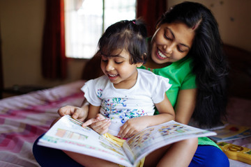 Little girl reading a book sitting on her mother's lap