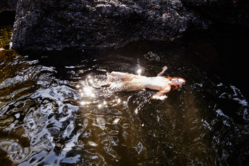 Beautiful redhead woman floating in water