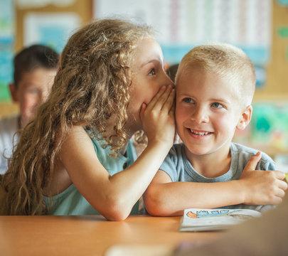 Girl Whispering Something to Her Classmate