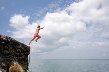 Summer fun - man jumping off cliff into the ocean