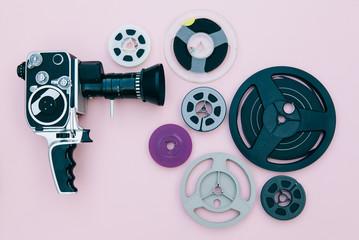 Vintage cinema camera and reels over pink background