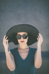 trendy young woman wearing hat and retro sunglasses