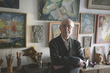 Portrait of old man standing on his studio of painting and sculpture