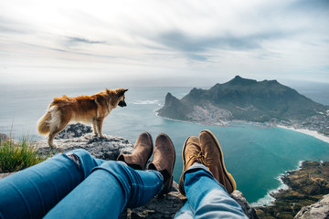 leather shoes and jeans of a relaxed hiking couple sitting at a mountain top with their dog