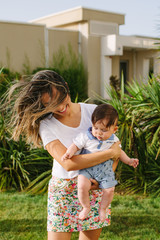 Beautiful windswept woman carrying young child in front of an apartment building
