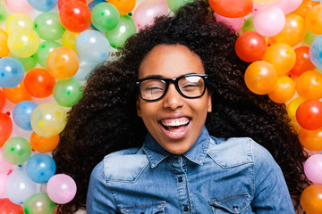 Young african woman playing with many colorful balloons