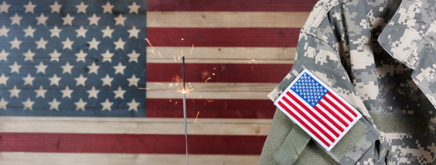 USA military uniform with rustic wooden flag of United States of America and sparkler in background