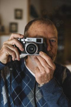 Senior man using an old film camera