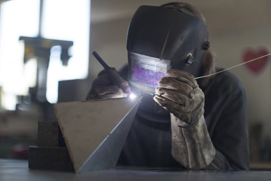 Blacksmith welding in workshop