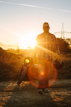wild, young and free - bearded casual biker walking along a road at sunset with his bike in the back