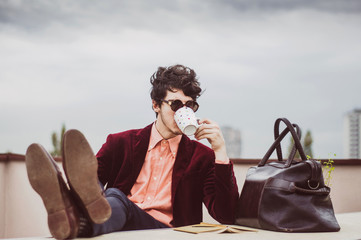Young business man relaxing with cup of coffee on teracce