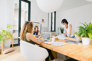 Three women working together to launch a creative startup