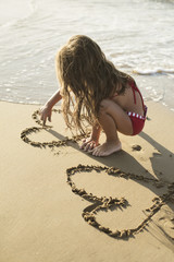 Child drawing in the sand