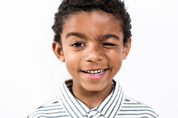 Little boy winking over white background