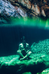 split perspective of a man holding a rock underwater meditating in a mountain river rock pool