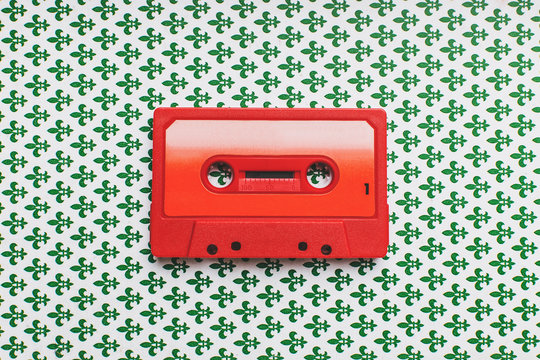 Red cassette tape on pattern background