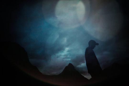 A man in a baseball cap walks into the dusk