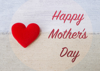 Happy Mother's day card concept, red heart with message on canvas fabric over white wood background