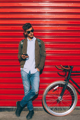 Stylish man with bicycle using phone outside