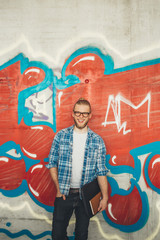 Smiling young man standing against colorful graffiti wall