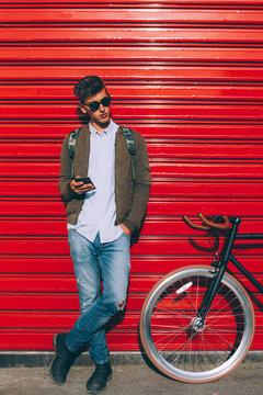 Stylish man with bicycle using phone outside