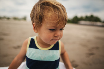 Funny toddler boy acting grumpy on beach wearing tank top