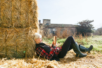 Woman resting on haystack on farm