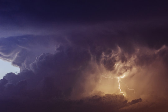 Lightning at sunset with a cloudy sky