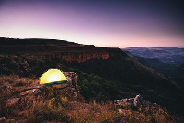 Tent at the edge of an escarpment overlooking a valley at dusk