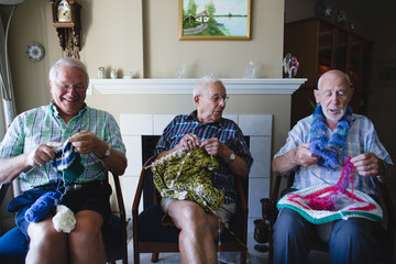 Group of senior men knitting together