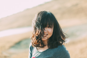 A female laughing with hair blocking her face
