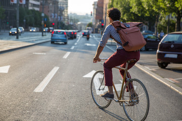 Young stylish man riding a bike to work
